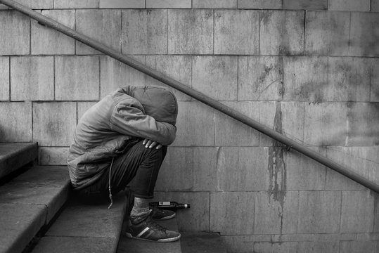 Drunk homeless man covered his face with his hands and sits on the stairs in the underpass, black and white photo.