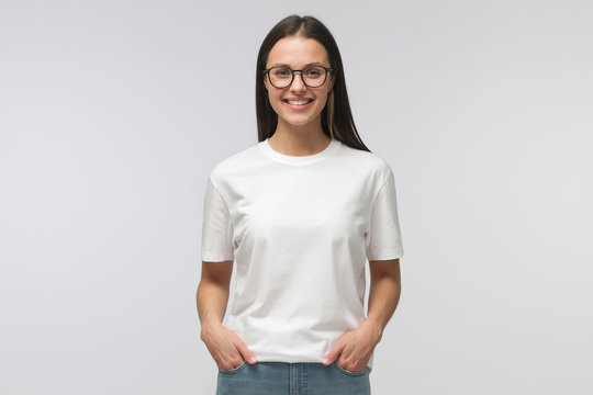 Young smiling woman standing with hands in pockets, wearing blank white tshirt with copy space, isolated on gray background