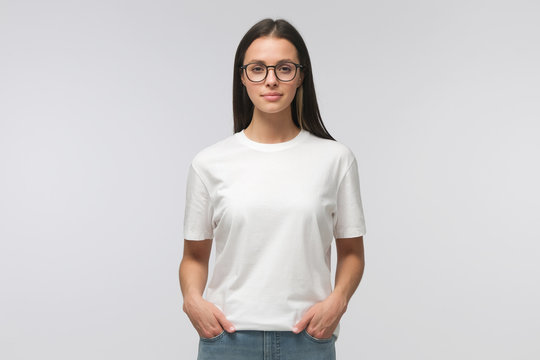 Young smiling woman in white t-shirt and trendy eyeglasses isolated on gray background
