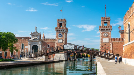 Venice. Panoramic view of Arsenal towers and canals. Girl in red goes on the bridge. Biennale,...