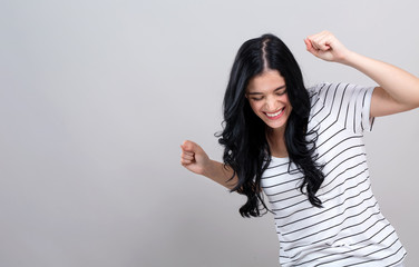 Young woman making a yay gesture on a gray background