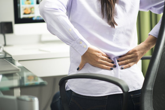Woman sitting at office having back pain due to bad position or having a not ergonomic chair