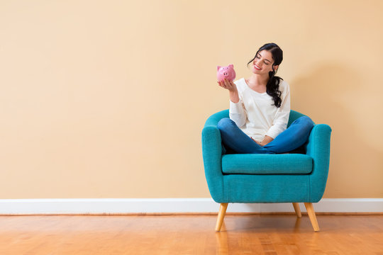 Young woman with a piggy bank sitting in a chair