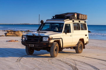 Western Australia – Outback adventure with 4WD vehicle at the beach of an ocean at sunrise with blue sky Wall mural