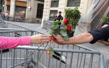 A woman gives flowers to a police officer guarding outside the National Police headquarters in Barcelona