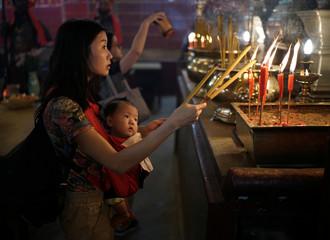 A woman burns candles as she prays at Man Mo Temple in Hong Kong