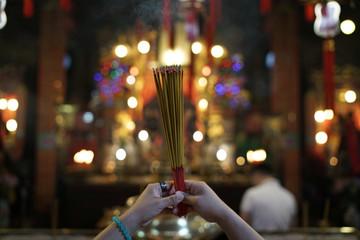 A woman burns incense as she prays at Man Mo Temple in Hong Kong