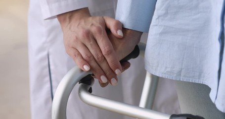 Fototapete - Female nurse holding old patient hand using walking frame, closeup