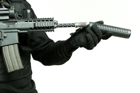 gloved hand of a man attaches a silencer to the barrel of an machine gun