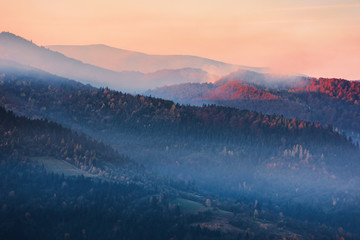 misty sunrise  in mountains. beautiful nature scenery in autumn. glowing fog on hills. magic moment of fall season