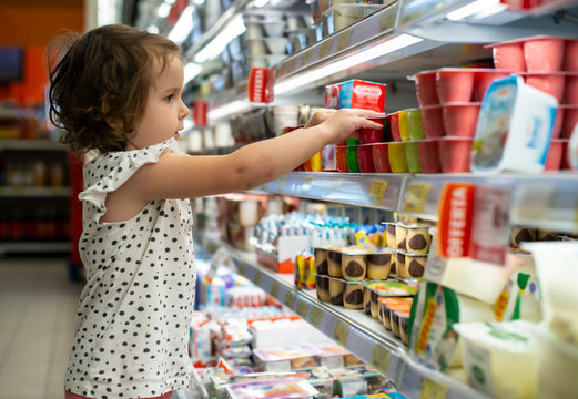 Little girl buying yogurt in supermarket. Child in supermarket select products