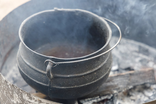 Old dirty pot on a bonfire in which wax melts