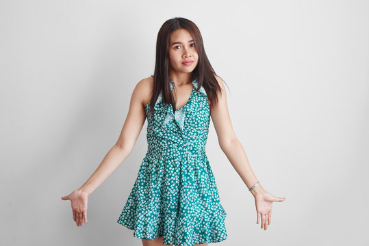 Asian Thai girl in green summer dress spreads her hands with regret, so what can I do it happened. White studio background