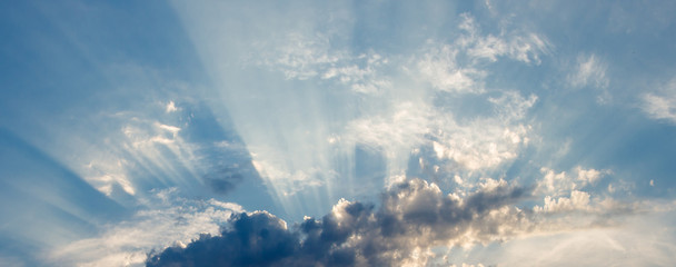 the sun's rays breaking through the clouds in straight lines, against a background of blue sky and thunderclouds
