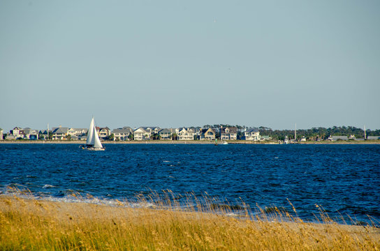 Sailboat sailing out of the Cape Fear river into the ocean at Oak Island. Baldhead Island in the background.