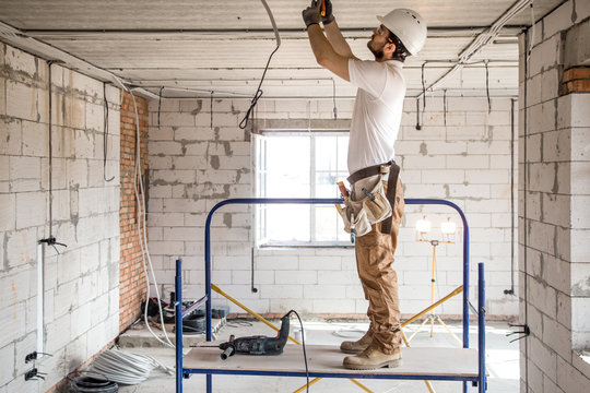 Electrician installer with a tool in his hands, working with cable on the construction site.