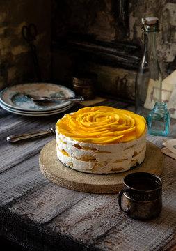 whole round tiramisu cake with white whipped cream and slices of ripe juicy mango on top
