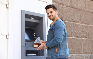 Young man with money near cash machine outdoors
