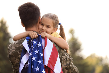 Father in military uniform with American flag and his daughter at sunny park