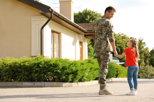 Father in military uniform with his little daughter outdoors