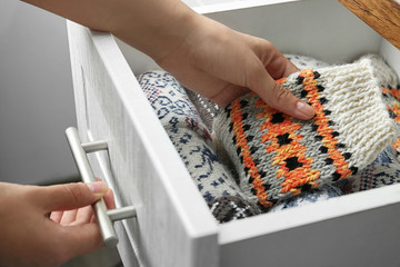 Fototapete - Woman taking warm knitted socks out of drawer, closeup
