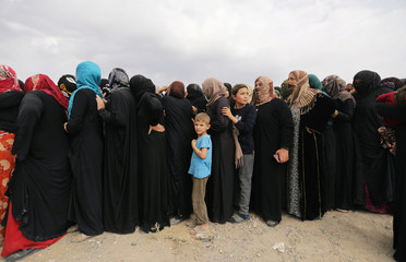 A boy stands in line as people receive aid donated by the Turkish Red Crescent in the border town of Tal Abyad