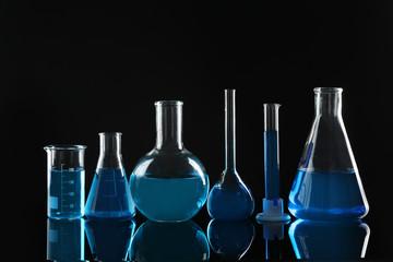 Fototapete - Laboratory glassware with blue liquids on black background