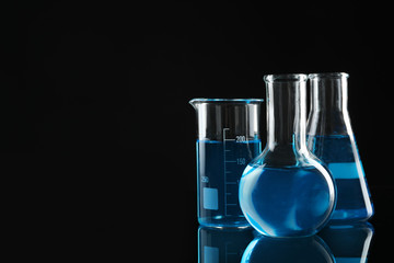 Fototapete - Laboratory glassware with blue liquids on black background. Space for text