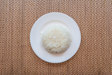 Cooked rice in plate on old wooden table..White jasmine streamed rice in a plate on a wooden table from top-view..Boiled rice.