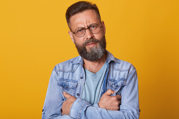 Isolated studio shot of young handsome bearded hipster man wearing trendy denim jacket, looking serious and pensive directly at camera. Caucasian male with stylish hair standing over yellow wall.