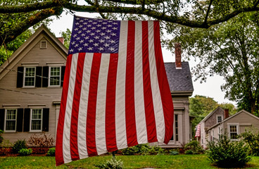 Brewster, Massachucetts, USA - September 3, 2006- An American flag hangs vertically in a tree outside a typical Cape Cod house beside Highway MA-6A on Labor Day.jpg