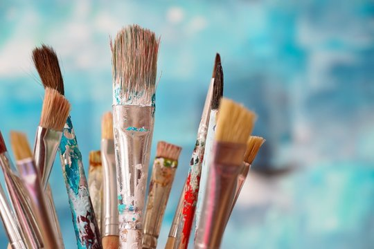 Paint brushes in front of blurred canvas
