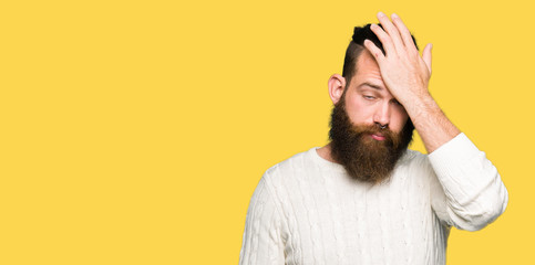 Young hipster man wearing winter sweater surprised with hand on head for mistake, remember error. Forgot, bad memory concept.