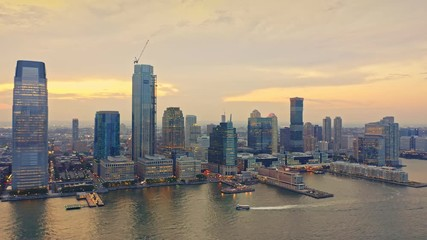 Fototapete - Drone footage with camera rotation and slow approach towards Jersey City skyline at sunset.
