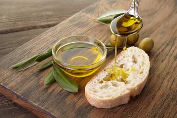 Fototapeta slice of bread seasoned with olive oil on wooden background obraz