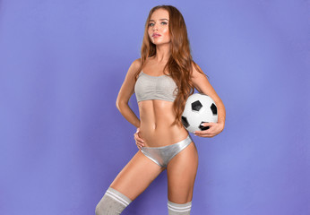 Sexy sporty girl with soccer ball posing on purple background.