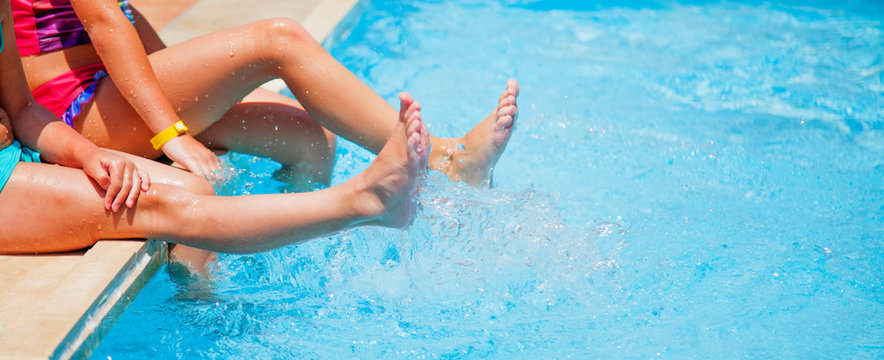Holidays in hot countries concept. Young girls legs splashing water in swimming pool.