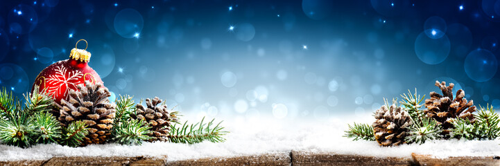 Christmas - Banner Of Red Ornament, Pine-cones And Branches On Snowy Wooden Table With Blue Bokeh Background Fotomurales