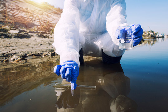 Conserve water and environment. Shot of an unrecognizable ecologist taking samples of water with test tube from city river to determine level of contamination and pollution.