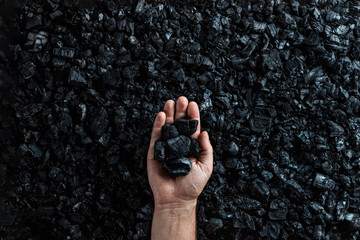 Male hand with coal on the background of a heap of coal, coal mining in an open pit quarry, copy space. Fossil fuels, environmental pollution.