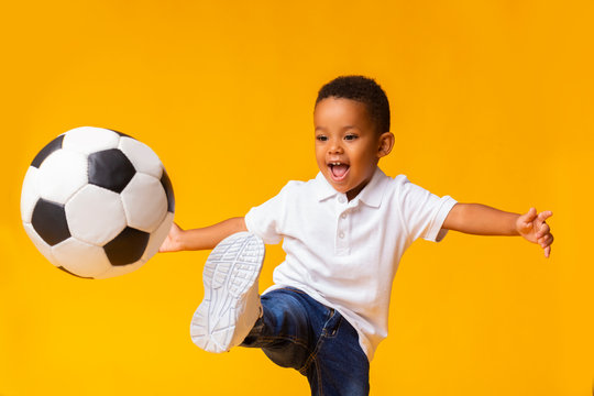 Adorable little boy playing football, hitting ball over yellow background