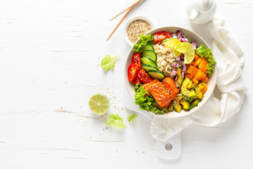 Buddha bowl with grilled salmon fish, fresh cucumber, tomato, onion, sweet pepper, avocado, lettuce salad and rice, healthy balanced eating