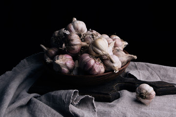 raw unpeeled garlic in a brown ceramic plate on a gray linen napkin