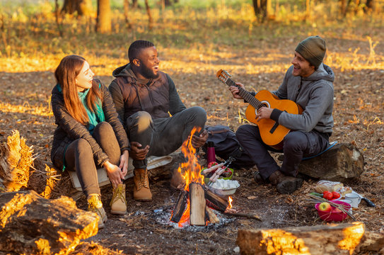 Group of people camping and singing in autumn woods