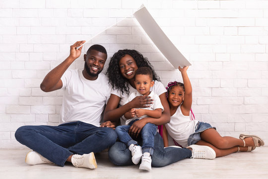 Happy African American Family Sitting On Floor Under Symbolic Roof
