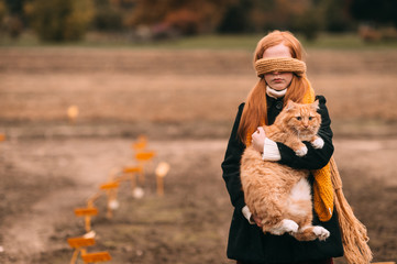 Redhead frekles blindfolded girl holding red cat in autumn field with lifeless landscape on background.