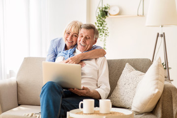 Happy senior couple having video call on laptop