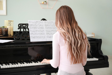 Young woman playing grand piano at home