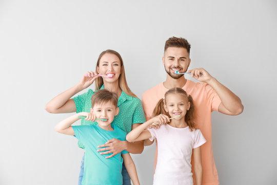 Portrait of family brushing teeth on light background