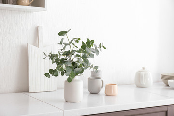 Vase with eucalyptus branches on table in kitchen Wall mural